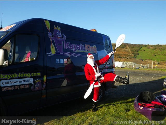 Father Christmas in front of kayak van