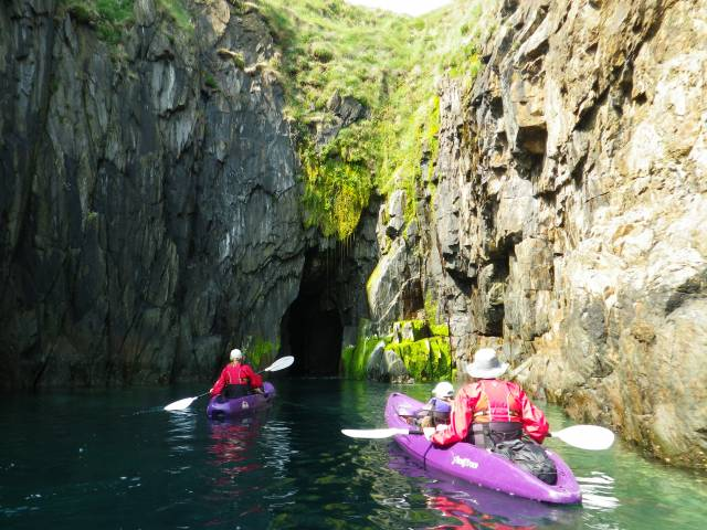 Family kayak towards a cave in Pembrokeshire, Wales