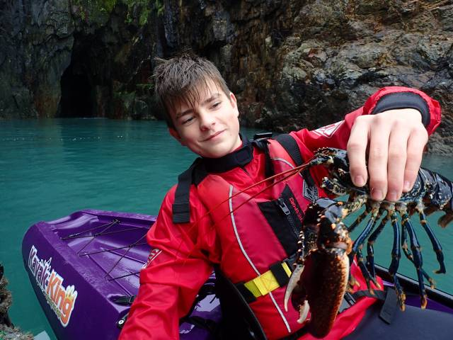 Holding a lobster while using a kayak gift voucher